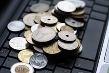 A Shot Of A Laptop And World Coins Royalty Free Stock Image