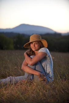 Teenage Girl Sitting In A Field Stock Photo