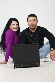 Free Couple Using Laptop On Wooden Floor Stock Images - 13993354