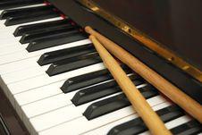 Diagonal Shot Of Drum Sticks On Piano Keyboard Stock Photo