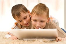Two Little Brothers Lie  With Laptop Stock Photography