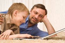 Father And Son On The Carpet With Laptop Stock Photography
