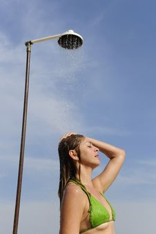 Woman Taking A Shower On The Beach