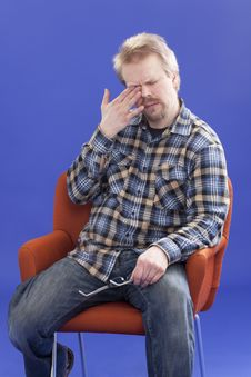 Tired Man Sitting On A Chair Royalty Free Stock Photography