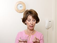 Free Older Woman Contemplates Taking A Pill Stock Photo - 14028690
