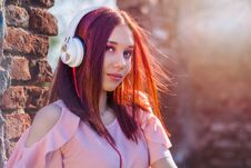 Gorgeous Redheads Lady Listening Music In Headphones On Blurred Background And Red Wall Bricks In Sunset Stock Images