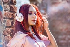 Gorgeous Redheads Lady Listening Music In Headphones On Blurred Outdoor Background And Wall Bricks Royalty Free Stock Photography