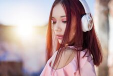 Gorgeous Redhead Lady Listening Music In Headphones On Blurred Background Outdoor Stock Photography