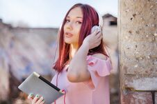 Free Redhead Woman With Headphones Using Tablet And Listening To Music On Old Ruins Building Royalty Free Stock Photos - 140325318