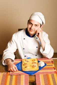 Handsome Young Chef In The Living Room With Cake O Royalty Free Stock Images