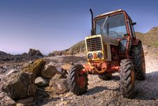 Free Old, Rusty Tractor On A Pebble Beach Stock Photography - 14053282