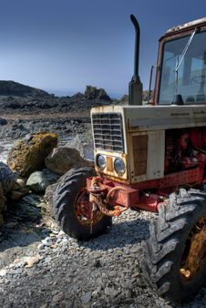 Frontside Of Old, Rusty Tractor On A Pebble Beach Stock Image