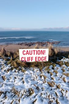 Red Caution Sign On A Cliff Edge