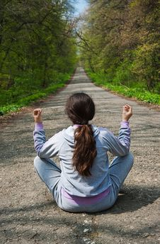 Girl Meditating, Sitting In The Middle Of The Road Royalty Free Stock Photos