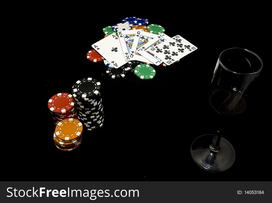 Royal flush, chips and glass of wine