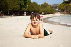 Happy Boy Lying At The Beach