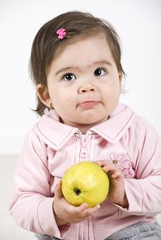 Sulky Baby Holding An Apple Stock Photo