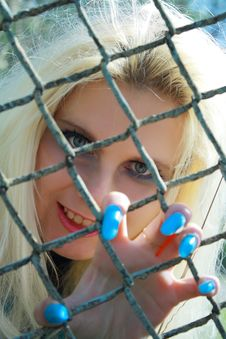 Free Portrait Blonde Stands Near Metallic Net Royalty Free Stock Image - 14084486