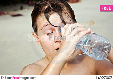 Free Young  Boy At The Beach  Looks Into A Bottle Royalty Free Stock Photography - 14097007
