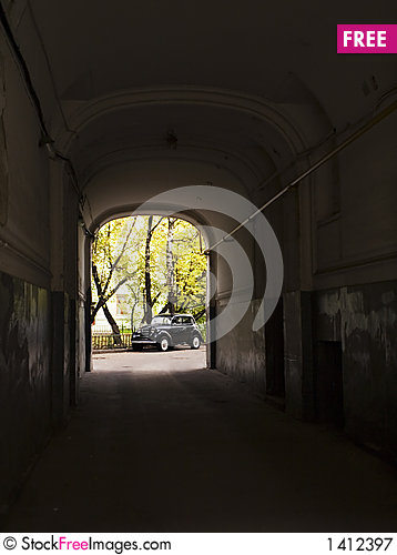 The old automobile stopped opposite to an arch Stock Photo