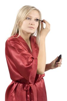 Free Young Woman Dressed Red Bathrobe Putting Mascara Royalty Free Stock Photography - 1416717