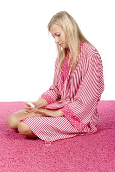 Free Young Woman Dressed Pink/white Bathrobe Painting Nails Royalty Free Stock Photography - 1416827