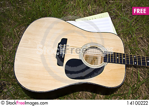 Free The Guitar And A Notebook For Music On The Lawn Stock Photography - 14100222