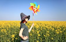 Girl In Cap With Wind Turbine At Rape Field. Stock Photo