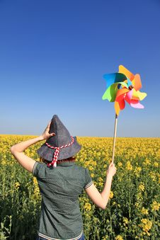 Girl In Cap With Wind Turbine At Rape Field.