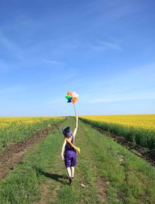 Girl With Wind Turbine At Rape Field. Royalty Free Stock Photo