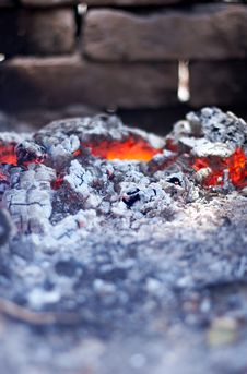 Burning Red Hot Coals On The Background Of Brick Stock Image