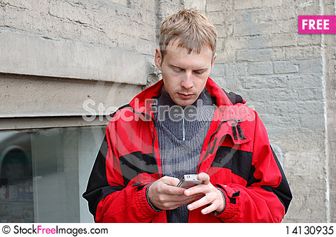 Blond man in red jacket talk on mobile phone. Stock Photo