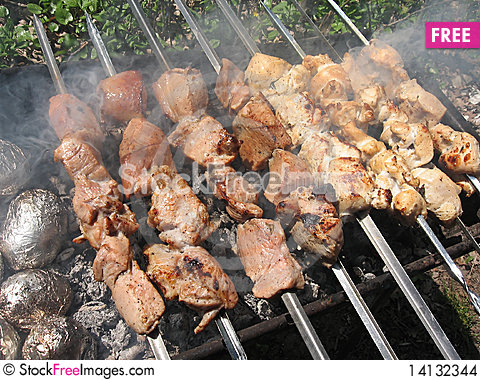 Meat skewers and baked potatoes in foil Stock Photo