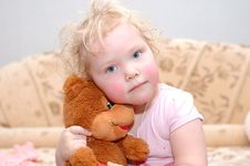 Pretty Curly Blond Girl With Toy Bear. Royalty Free Stock Photo