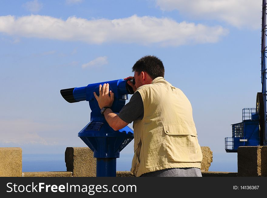 Man looking through a coin operated binoculars