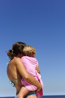Mother Carrying Her Daughter On The Beach Stock Photography