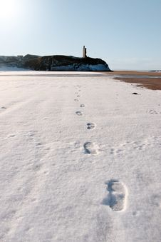 Footprints In Snow On  Beach With Castle
