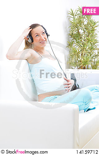 Free Piregnant Woman Sits On A Sofa And Listens To Musi Stock Photography - 14159712