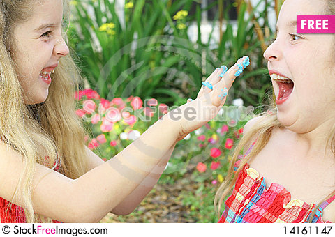 Free Little Girl Putting Frosting On Sister Royalty Free Stock Photography - 14161147