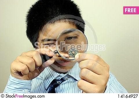 Free A Boy Examining A Coin Royalty Free Stock Photography - 14164927