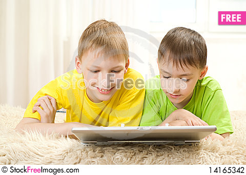 Free Two Little Brothers Lie  With Laptop Stock Photography - 14165342