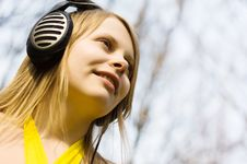 Blond Woman Smiling Listening Music In Headphones