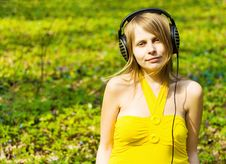 Blond Girl Listening Music In Headphones Outdoors