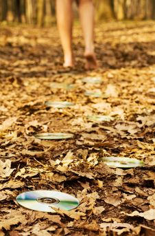 Woman S Legs Leaving Audio Discs On Leaves Royalty Free Stock Photography