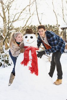 Free Teenage Couple Building Snowman Stock Image - 14188681