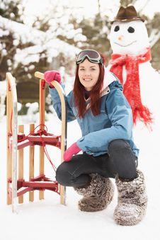 Free Teenage Girl With Sledge Next To Snowman Royalty Free Stock Photos - 14188728
