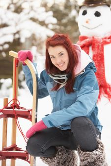 Free Teenage Girl With Sledge Next To Snowman Stock Photo - 14188730