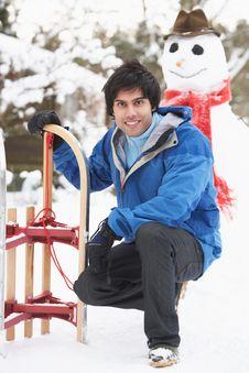 Free Teenage Boy With Sledge Next To Snowman Stock Photos - 14188733