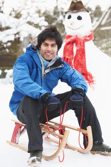 Free Teenage Boy With Sledge Next To Snowman Stock Images - 14188734