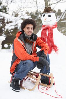 Free Man With Sledge Next To Snowman Stock Image - 14188751